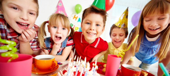 Group of adorable kids gathered around birthday cake with candles